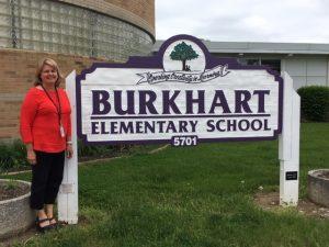 Joann Ahman in front of burkhart elementary sign