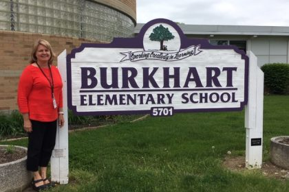 Joann Ahman in front of burkhart elementary sign
