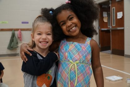 Two preschool girls hugging
